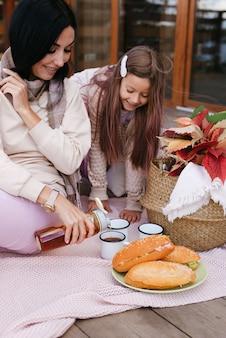 Une maman et une fille drôles versent le thé d'un thermos dans des tasses