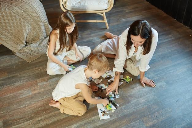 Maman fille et fils ont mis le puzzle ensemble sur la cheminée