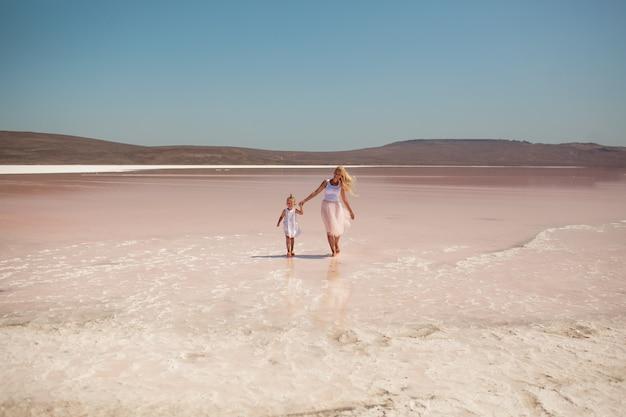 Maman et fille heureuse vont par la main au lac rose, vêtues de couleurs vives, maman a les cheveux longs blonds