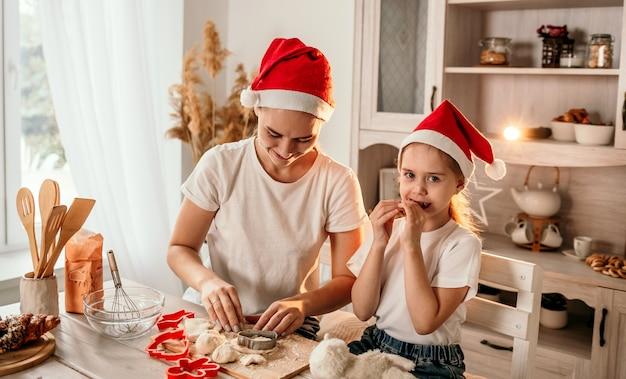 Une maman et une fille heureuses en chapeaux de noël sont assises à table dans la cuisine et pétrissent la pâte