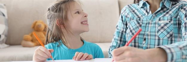 Maman et fille heureuses dessinent avec des crayons sur papier