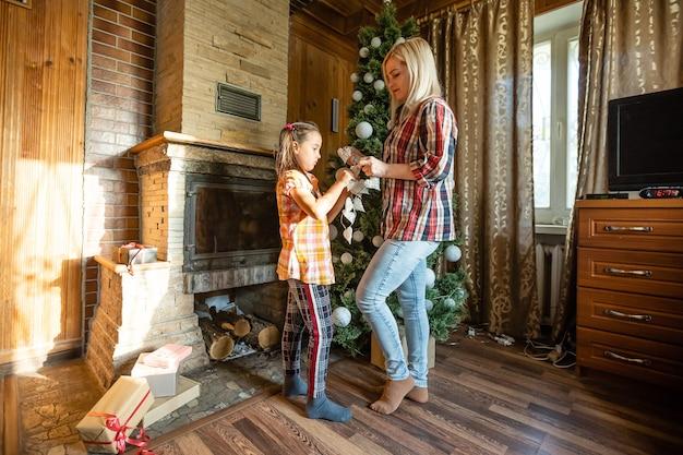 Maman et fille jouant avec des balles près de l'arbre de noël. cadeaux, lumières, boules en arrière-plan.