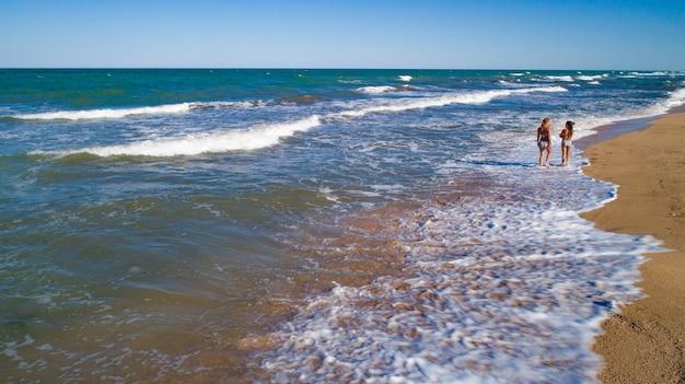 Maman et fille marchent à travers les vagues le long de la mer