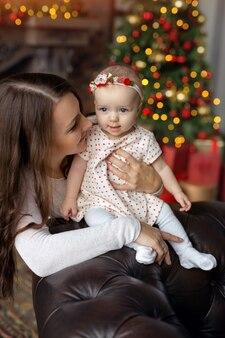 Maman et fille mignonnes sur un arrière-plan flou avec un arbre de noël