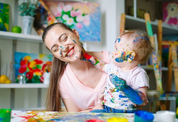 Maman et fille peignent sur toile à l'école de dessin.