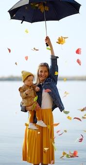 Maman et fille sur la plage avec parasol avec des feuilles.