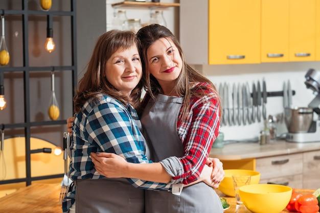 Maman et fille posant dans la cuisine familiale