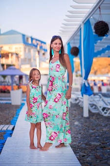 Maman et fille en robes identiques marcher le long d'un chemin en bois sur une plage de galets au bord de la mer dans la zone touristique