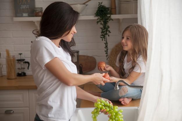 Maman et fille souriantes lavant des fruits dans une cuisine de style scandinave.