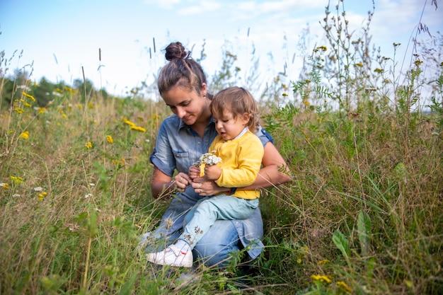 Maman et fille tout-petit recueillent un bouquet de fleurs sauvages fleurs millefeuille close-up