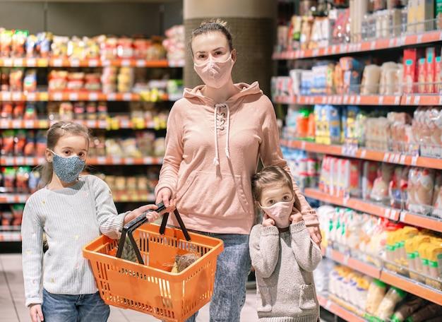 Maman et filles achètent des masques au magasin pendant la quarantaine en raison de la pandémie de coronavirus.