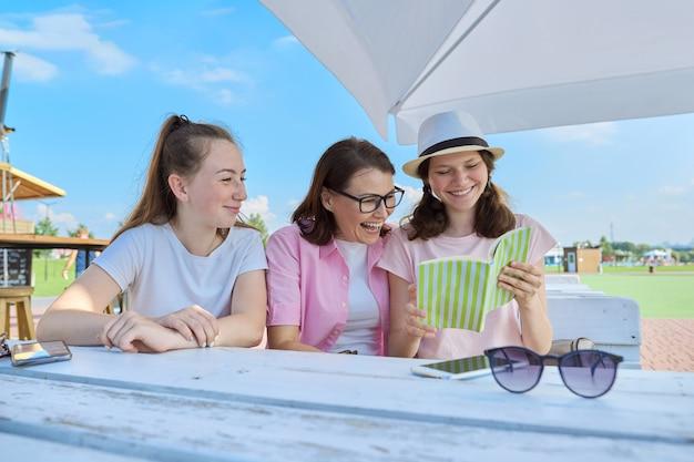 Maman et filles adolescentes s'amusent, regardent et lisent un livre amusant.