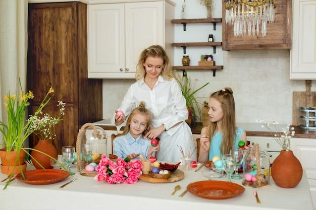 Maman et filles sont engagées à peindre des œufs de pâques dans la cuisine