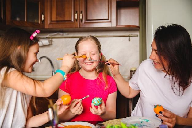 Maman et filles en train de colorier les œufs de pâques se moquent de salir le nez de la fille.