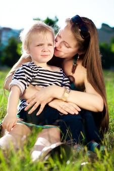 Maman avec le fils assis sur une herbe verte