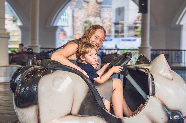 Maman et fils ayant un tour dans la voiture tamponneuse au parc d'attractions.