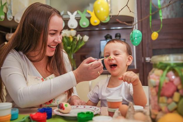 Maman et fils dans le processus de peinture aux oeufs de pâques imbécile avec des peintures dans la cuisine décorée à la maison