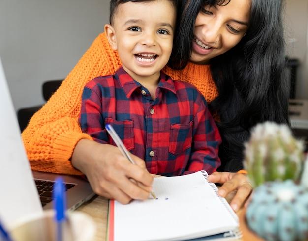 Maman avec fils dessin dans un ordinateur portable au bureau