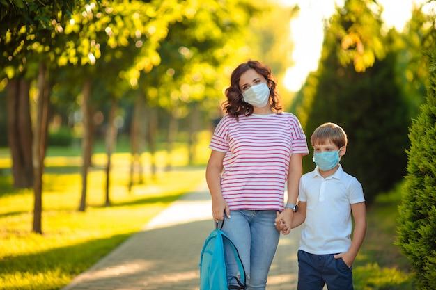 Maman et fils écolier dans des masques médicaux sur le chemin de l'école