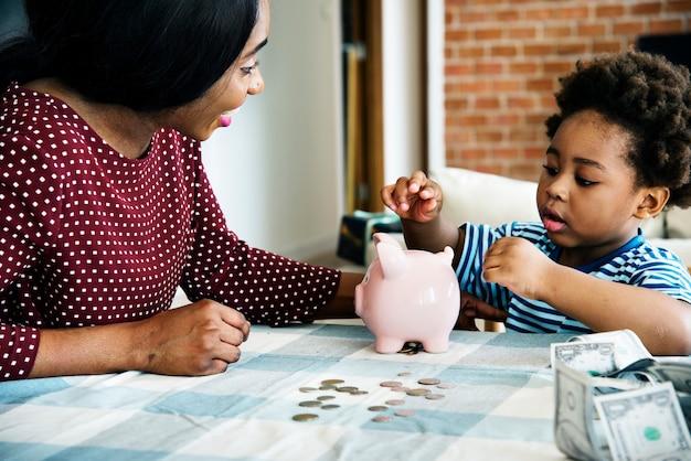 Maman et fils économiser de l'argent à la tirelire