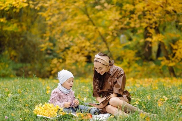 Maman et fils marchant et s'amusant ensemble dans le parc d'automne.