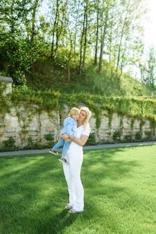 Maman et fils sur pelouse verte. maman tient son garçon dans ses bras.