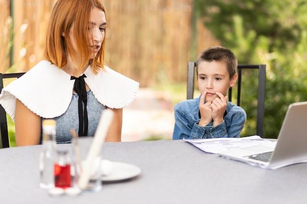 Maman et garçon écolier sont engagés dans des cours via un ordinateur portable à la maison dans le jardin. cours en ligne pour enfants. l'écolier écoute une conférence et résout des problèmes