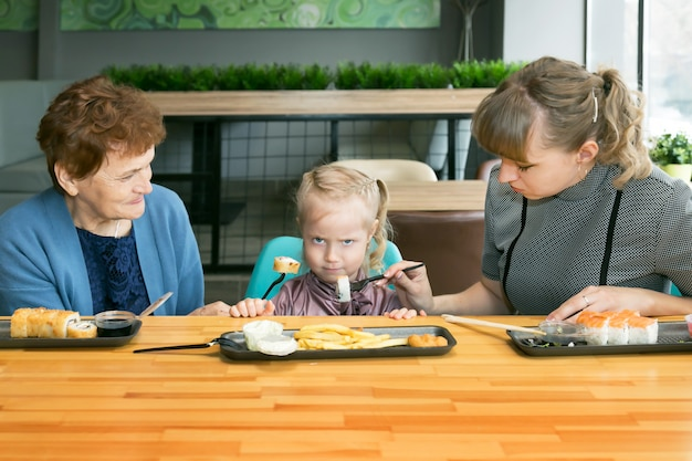 Maman et grand-mère nourrissent la petite fille ensemble.