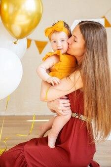 Une maman heureuse embrasse sa fille d'un an vêtue de vêtements jaunes, photo de studio pendant un an de l'enfant