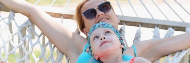Maman heureuse avec sa fille swing sur swing dans la nature