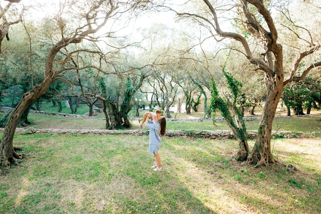 Maman jette l'enfant embrasse et joue avec lui parmi les arbres de l'oliveraie