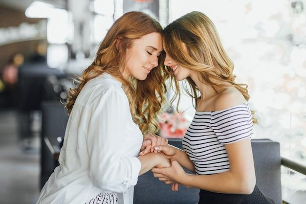 Maman et jeune belle adolescente se tiennent la main sur le café terrasse d'été dans des vêtements décontractés. ils sont contents.