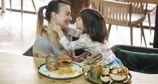 Maman avec une jolie fille mangeant de la restauration rapide dans un café
