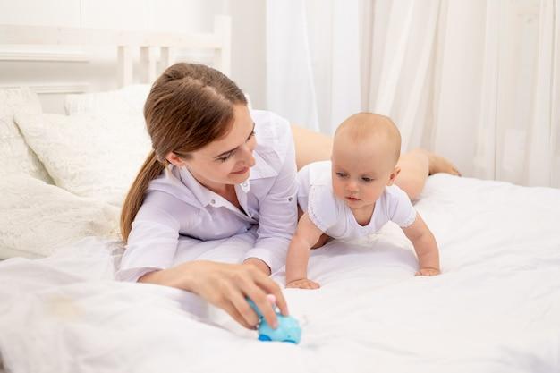 Maman jouant avec bébé 6 mois allongé sur un lit blanc, maman de loisirs avec bébé, place pour le texte