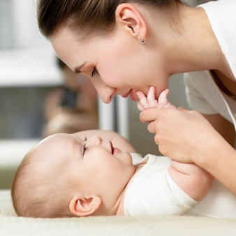 Maman joue avec le bébé 6 mois sur le lit à la maison