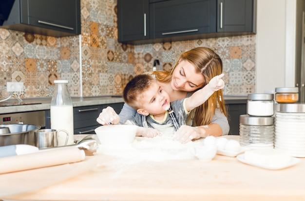 Maman joue avec enfant dans la cuisine. la cuisine est faite est de couleurs sombres et de style roustique.