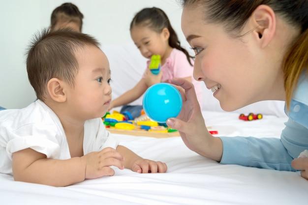 Maman joue avec son bébé dans la chambre.