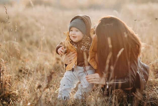 Maman joue avec son petit bébé garçon, famille heureuse à pied