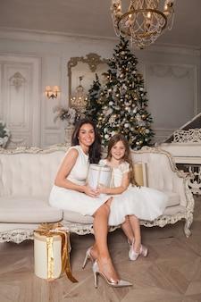 Maman joyeuse et sa fille mignonne fille échangeant des cadeaux dans un intérieur classique blanc dans le contexte d'un piano et d'un arbre de noël décoré.