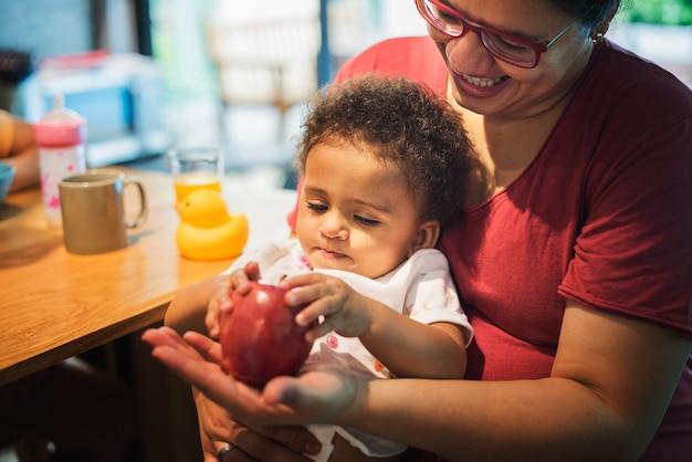 Maman laisse sa fille jouer à la pomme