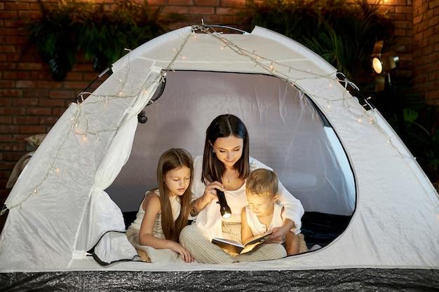 Maman lit aux enfants une histoire au coucher assis dans une tente à la maison. mère fils et fille étreignent et lisent un livre avec une lampe de poche dans leurs mains