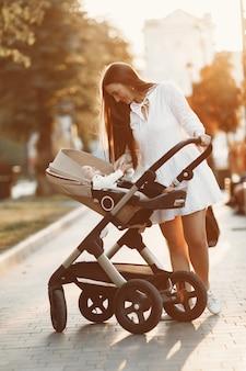 Maman marchant sur la rue de la ville. femme poussant son tout-petit assis dans un landau. concept de famille.