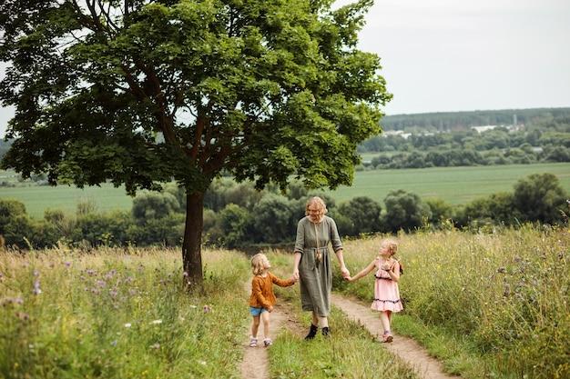 Maman marche avec ses enfants dans un pré en été. avoir un week-end en famille en plein air. concept de vie authentique.