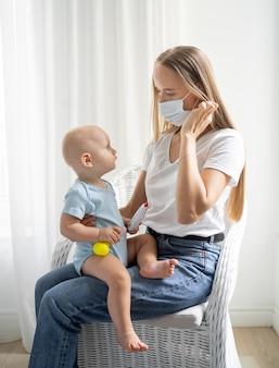 Maman avec masque médical tenant l'enfant à la maison pendant la quarantaine