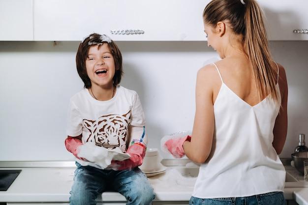 Maman ménagère en gants roses lave la vaisselle avec son fils à la main dans l'évier avec du détergent