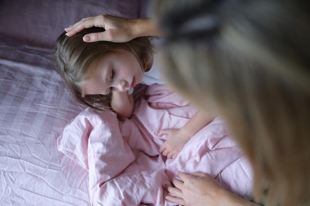 Maman met une fille triste sur la tête avant d'aller se coucher.