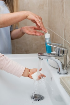 Maman, mettre du savon sur la main de l'enfant pour se laver