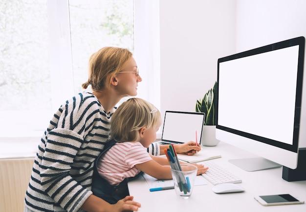 Une maman moderne équilibre entre le travail et l'enseignement à domicile des enfants en congé de maladie ou en quarantaine