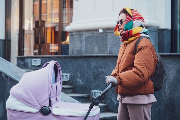 Maman moderne à la mode avec une poussette lors d'une promenade en ville, automne. maman conduit une poussette dans les rues, gros plan.