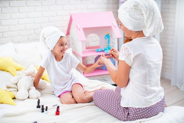 Maman montre à sa fille comment faire une manucure.